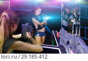 Купить «Excited people playing enthusiastically laser tag game», фото № 29185412, снято 27 августа 2018 г. (c) Яков Филимонов / Фотобанк Лори
