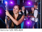 Купить «Positive girl holding laser pistol during playing lasertag game», фото № 29185424, снято 27 августа 2018 г. (c) Яков Филимонов / Фотобанк Лори