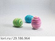 Купить «Easter eggs wrapped woolen string on a white wool background», фото № 29186964, снято 21 ноября 2018 г. (c) Владимир Пойлов / Фотобанк Лори