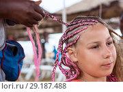 Купить «Плетение косичек в африканском стиле, загорелая девочка с розовыми дредами», фото № 29187488, снято 19 июля 2018 г. (c) Кекяляйнен Андрей / Фотобанк Лори