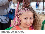 Купить «Девочке заплетают косы в африканском стиле, с розовыми веревочками», фото № 29187492, снято 19 июля 2018 г. (c) Кекяляйнен Андрей / Фотобанк Лори