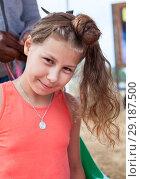 Купить «Девочке делают прическу на пляже», фото № 29187500, снято 19 июля 2018 г. (c) Кекяляйнен Андрей / Фотобанк Лори
