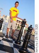 Купить «Подросток стоит возле большой черной фигуры шахматного короля, уличные шахматы», фото № 29187520, снято 26 июля 2018 г. (c) Кекяляйнен Андрей / Фотобанк Лори