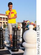 Купить «Подросток задумался над следующим ходом во время игры в уличные шахматы», фото № 29187524, снято 26 июля 2018 г. (c) Кекяляйнен Андрей / Фотобанк Лори