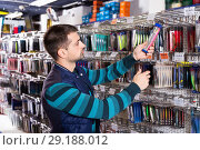 Купить «Man customer choosing fishing lures near stand in the sports shop», фото № 29188012, снято 16 января 2018 г. (c) Яков Филимонов / Фотобанк Лори