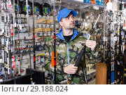 Купить «Male consumer in fishing clothing holding fishing rod», фото № 29188024, снято 16 января 2018 г. (c) Яков Филимонов / Фотобанк Лори
