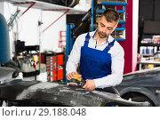 Купить «Mechanic grinding car bumper», фото № 29188048, снято 4 апреля 2018 г. (c) Яков Филимонов / Фотобанк Лори