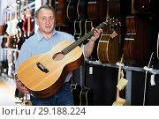 Купить «Mature man choosing acoustic guitar», фото № 29188224, снято 18 сентября 2017 г. (c) Яков Филимонов / Фотобанк Лори