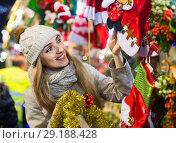 Купить «Beautiful smiling young woman choosing Christmas decoration», фото № 29188428, снято 18 октября 2018 г. (c) Яков Филимонов / Фотобанк Лори