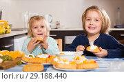 Купить «Two little girls enjoying pastry with cream», фото № 29188440, снято 14 декабря 2018 г. (c) Яков Филимонов / Фотобанк Лори
