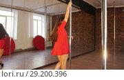 Sexy girl in red dress pole dance. Spinning around the pole. Стоковое видео, видеограф Константин Шишкин / Фотобанк Лори