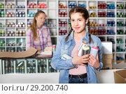Купить «Portrait of girl choosing paint color in aerosol can in art shop», фото № 29200740, снято 12 апреля 2017 г. (c) Яков Филимонов / Фотобанк Лори