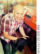 Купить «Professional efficient craftsman polishing footwear», фото № 29200956, снято 19 декабря 2018 г. (c) Яков Филимонов / Фотобанк Лори