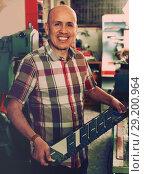Купить «Diligent senior man doing vehicle numbers on machine», фото № 29200964, снято 16 октября 2018 г. (c) Яков Филимонов / Фотобанк Лори