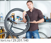 Купить «young man shows modern bicylce tires in the bike store.», фото № 29201140, снято 14 мая 2018 г. (c) Яков Филимонов / Фотобанк Лори