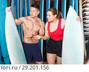 Купить «Young couple planning to surf, choosing boards and surfing suits in beach club», фото № 29201156, снято 30 апреля 2018 г. (c) Яков Филимонов / Фотобанк Лори