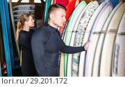 Купить «Young couple planning to surf, choosing boards and surfing suits in beach club», фото № 29201172, снято 30 апреля 2018 г. (c) Яков Филимонов / Фотобанк Лори