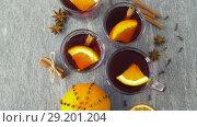 Купить «glasses of hot mulled wine with orange and spices», видеоролик № 29201204, снято 7 октября 2018 г. (c) Syda Productions / Фотобанк Лори