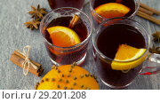 Купить «glasses of hot mulled wine with orange and spices», видеоролик № 29201208, снято 7 октября 2018 г. (c) Syda Productions / Фотобанк Лори