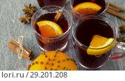 Купить «glasses of hot mulled wine with orange and spices», видеоролик № 29201208, снято 7 октября 2018 г. (c) Syda Productions / Фотобанк Лори