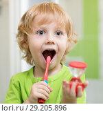 Купить «Happy kid boy brushing teeth in bathroom. He is monitoring lasting of cleaning action with hourglass.», фото № 29205896, снято 22 мая 2019 г. (c) Оксана Кузьмина / Фотобанк Лори