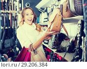 Купить «Excited young female selecting new handbag», фото № 29206384, снято 19 января 2019 г. (c) Яков Филимонов / Фотобанк Лори