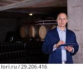 Купить «Winemaker with clipboard in winery vault», фото № 29206416, снято 22 января 2018 г. (c) Яков Филимонов / Фотобанк Лори