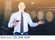 Купить «Male winemaker giving tour around winery, inviting to tasting red wine», фото № 29206424, снято 22 января 2018 г. (c) Яков Филимонов / Фотобанк Лори