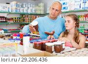 Купить «Daughter with father looking goods in grocery store», фото № 29206436, снято 4 июля 2018 г. (c) Яков Филимонов / Фотобанк Лори