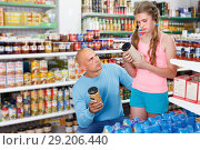 Купить «Preteen girl with father choosing different goods in shop», фото № 29206440, снято 4 июля 2018 г. (c) Яков Филимонов / Фотобанк Лори