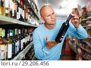 Купить «Focused man customer looking bottle of red wine in winery shop», фото № 29206456, снято 4 июля 2018 г. (c) Яков Филимонов / Фотобанк Лори