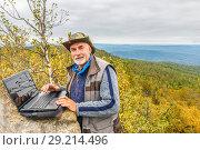 Купить «Mature male tourist is working on a laptop on top of the High Mountain.», фото № 29214496, снято 6 сентября 2017 г. (c) Акиньшин Владимир / Фотобанк Лори