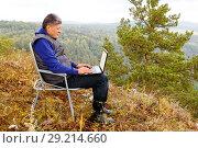 Купить «Mature male tourist is working on a laptop on top of the High Mountain.», фото № 29214660, снято 9 сентября 2017 г. (c) Акиньшин Владимир / Фотобанк Лори