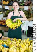 Купить «Portrait of smiling saleswoman with cluster of yellow bananas in store», фото № 29215304, снято 14 октября 2017 г. (c) Яков Филимонов / Фотобанк Лори
