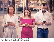Купить «Young people are focusing on smartphones during a together walking outdoors.», фото № 29215332, снято 18 октября 2017 г. (c) Яков Филимонов / Фотобанк Лори