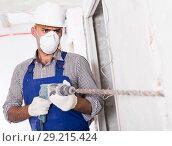 Купить «Portrait of repairer male working with drill indoors», фото № 29215424, снято 18 мая 2017 г. (c) Яков Филимонов / Фотобанк Лори