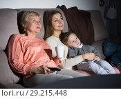 Купить «Woman with her mother and son are watching film in time evening rest», фото № 29215448, снято 15 февраля 2018 г. (c) Яков Филимонов / Фотобанк Лори
