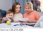 Купить «Woman is talking her mother how to fill utility bills with laptop», фото № 29215456, снято 15 февраля 2018 г. (c) Яков Филимонов / Фотобанк Лори