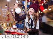 Купить «Beautiful young girl choosing Christmas decoration», фото № 29215616, снято 22 декабря 2016 г. (c) Яков Филимонов / Фотобанк Лори