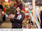 Купить «Smiling young woman choosing christmas tree», фото № 29215624, снято 22 декабря 2016 г. (c) Яков Филимонов / Фотобанк Лори