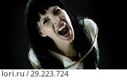 Crazy bloody scary zombie woman screams at camera. Стоковое фото, фотограф katalinks / Фотобанк Лори