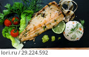 Купить «deliciously fried trout fillet with rice and greens on black plate», видеоролик № 29224592, снято 17 сентября 2018 г. (c) Яков Филимонов / Фотобанк Лори