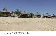 Waves of the warm sea run on the sandy beach of the tropical resort with umbrellas and chaise lounges. Стоковое видео, видеограф Куликов Константин / Фотобанк Лори