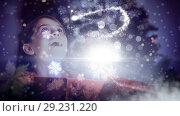 Купить «Excited girl opening magical Christmas gift box with sparkling light», видеоролик № 29231220, снято 16 июля 2019 г. (c) Wavebreak Media / Фотобанк Лори