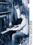 Купить «Father and son are looking keyboard», фото № 29231696, снято 29 марта 2017 г. (c) Яков Филимонов / Фотобанк Лори