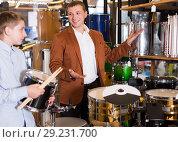 Купить «Father and teenage son examining drum units in guitar shop», фото № 29231700, снято 29 марта 2017 г. (c) Яков Филимонов / Фотобанк Лори