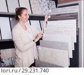 Купить «Woman looking at ceramic tile», фото № 29231740, снято 4 апреля 2017 г. (c) Яков Филимонов / Фотобанк Лори