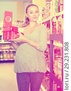 Купить «Pregnant woman is demonstrating her choice in supermarket.», фото № 29231808, снято 5 июня 2017 г. (c) Яков Филимонов / Фотобанк Лори