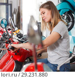 Купить «Smiling female is looking on new motobikes», фото № 29231880, снято 8 мая 2018 г. (c) Яков Филимонов / Фотобанк Лори