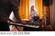 Купить «Repetition. Guy plays on keyboards, girl drummer at the backgrond. Backlights. Focus on hands. View from back of guy.», видеоролик № 29233004, снято 8 июля 2020 г. (c) Константин Шишкин / Фотобанк Лори
